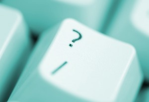 a keyboard question mark key under warm colour lighting
